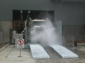 Truck passing through wheel wash system