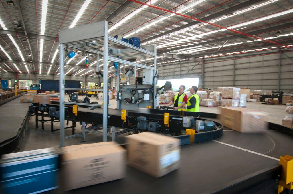 Dimension Weigh Scan induct lane for Parcels merging into a carousel conveyor